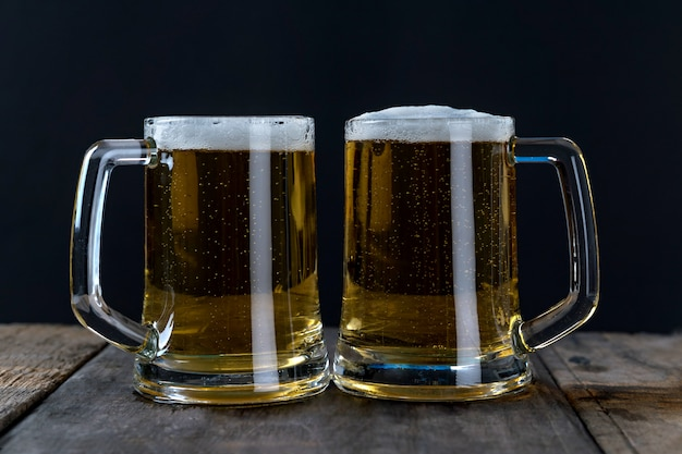 木製のテーブルと黒の背景上のガラスのビール