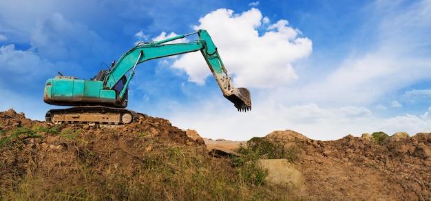 青い空の下で工事現場に取り組んでいる掘削機のパノラマ