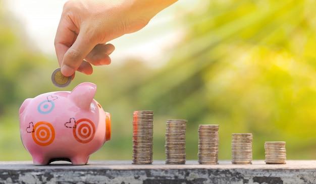 お金を節約、ぼやけた庭の背景の上に貯金箱にコインを入れて手