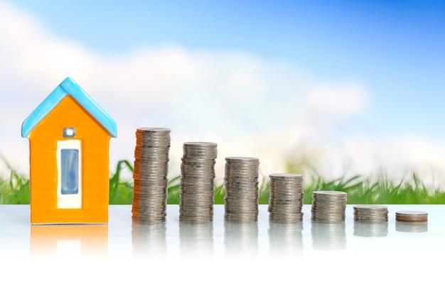 小さな家と黒い背景にコイン