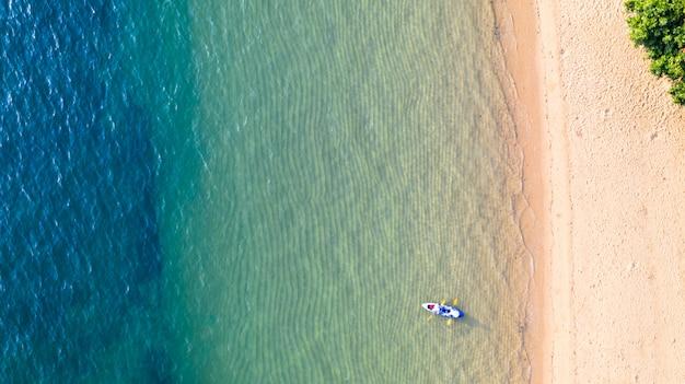 日陰のエメラルドブルーの水と波の泡の背景を持つ海の周りカヤックの空中のトップビュー