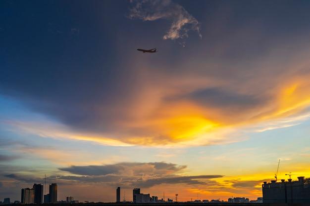 夕暮れの空を飛んでいる飛行機と夕暮れ時のバンコクのシルエット