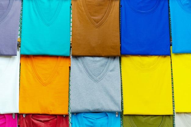 Крупным планом красочные футболки на вешалках