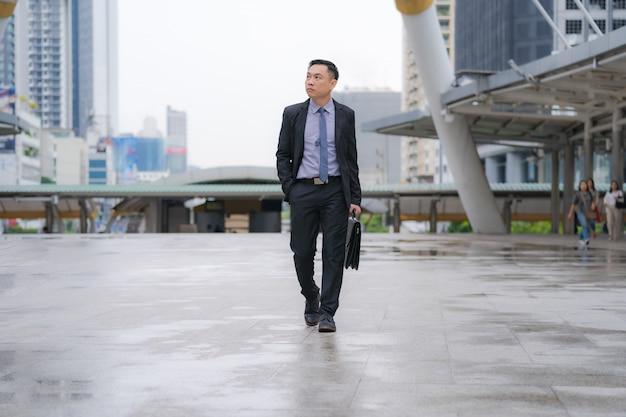 アジア系のビジネスマンが歩くとビジネスオフィスビルとブリーフケースを保持