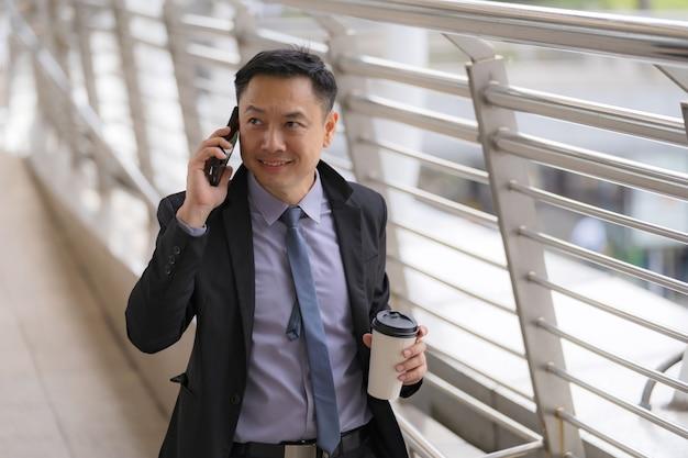 アジア系のビジネスマンが歩くと携帯電話で話している
