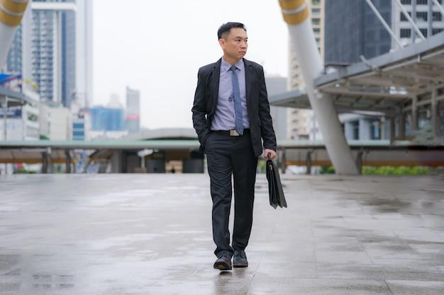 アジア系のビジネスマンが歩いていると市内のビジネスオフィスビルとブリーフケースを保持