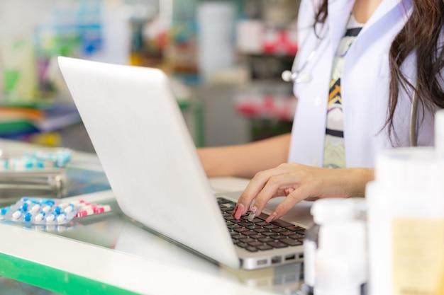 Улыбаясь и счастлив азиатского женского фармацевта, работающего с ноутбуком в аптеке