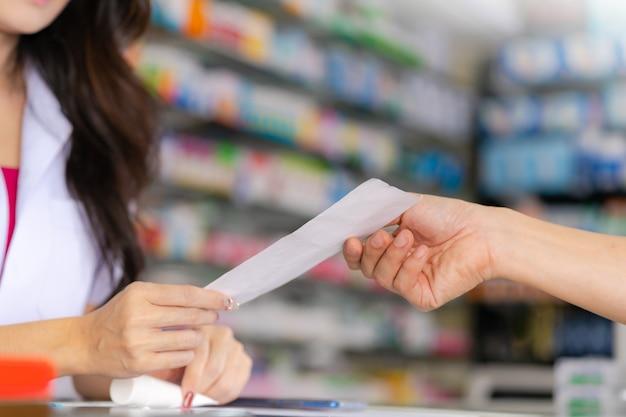 薬局で患者の男性に薬の処方を読む女性薬剤師