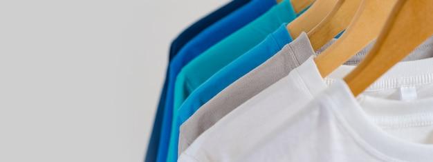 Крупным планом красочные футболки на вешалках, одежда фон