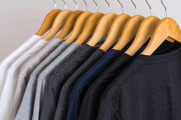 Крупным планом футболки на вешалках, одежда фон