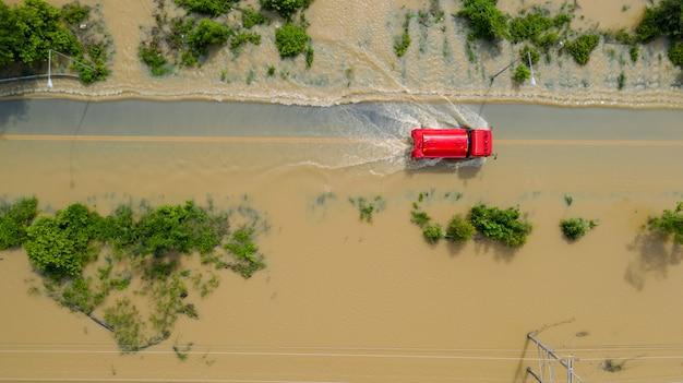 Вид сверху с воздуха на затопленную деревню и проселочную дорогу с красной машиной