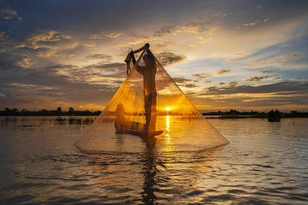 夕暮れ時、タイの湖でネットで漁船の漁師のシルエット