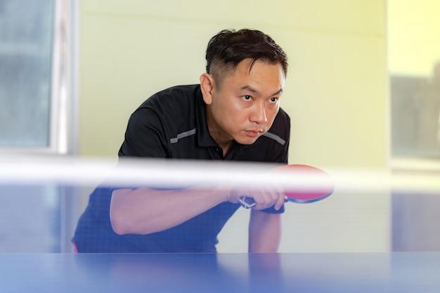 Стол для пинг-понга, мужчина играет в настольный теннис с ракеткой и мячом в спортивном зале