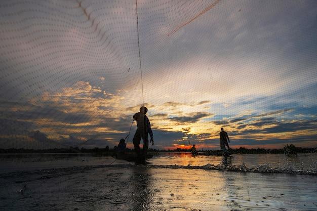 Силуэт рыбака на рыбацкой лодке с сетью на озере на закате, таиланд
