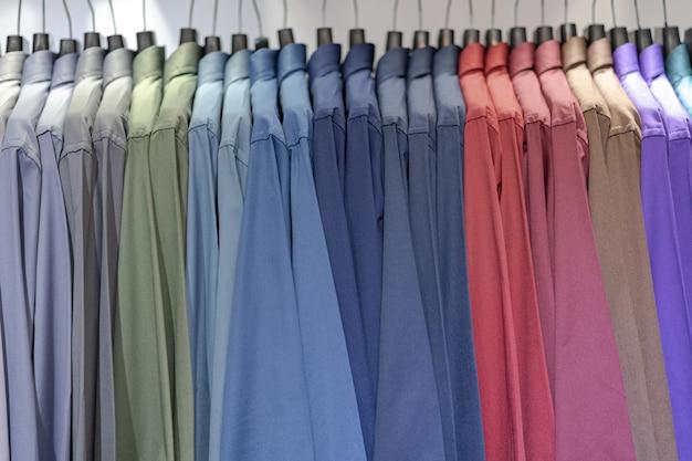 Закройте разноцветные рубашки на вешалках, красочный фон ткани одежды