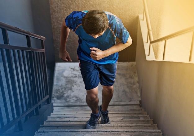 Спортсмен бегун бежит по ступенькам лестницы