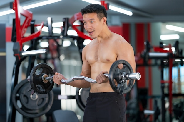 ジムで重いバーベルでトレーニングスポーティな男
