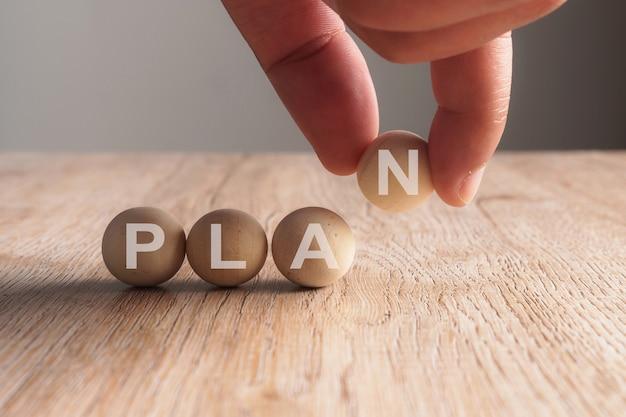 木のボールで書かれた計画の言葉に手を置く