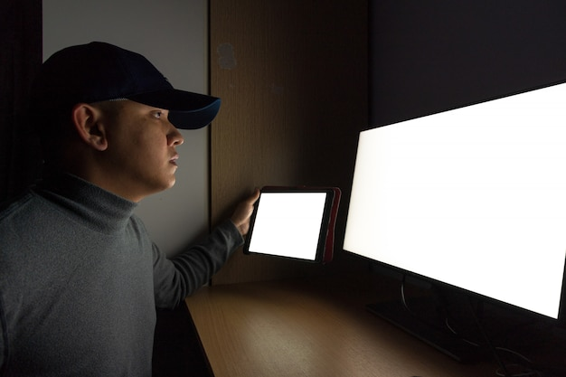 Боковой вид человека хакер сидит на мониторе компьютера, белый экран планшет в темной комнате.