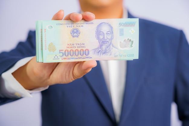 Деньги во вьетнаме держат на руках деловой человек в синем костюме
