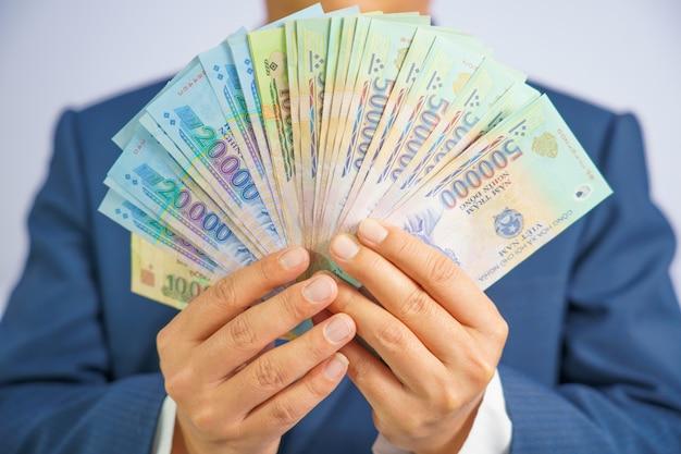 ベトナムのお金は青いスーツを着てビジネス男を手に保持します。