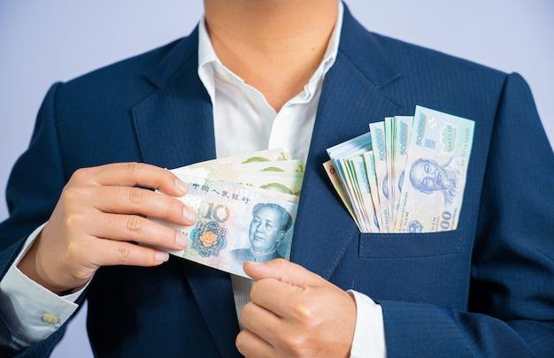 中国のお金は、ビジネスマンとベトナムドンのお金を手に保持します