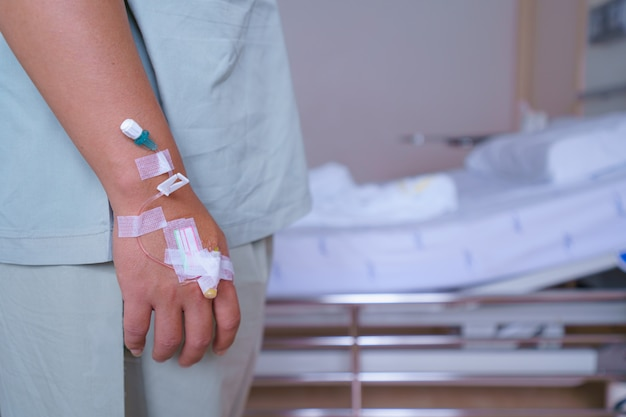 Пациенты мужчина цитирует в больнице, стоя у кровати больного больного