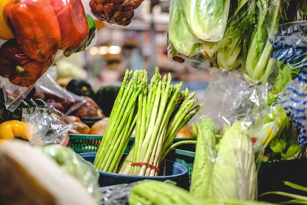 新鮮なアスパラガスのオフィシナリスは、地元の市場でさまざまな野菜をテーブルに置いています。