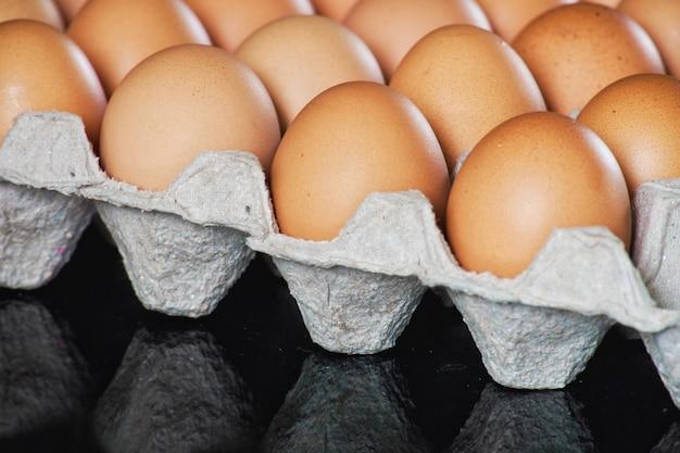 Свежие куриные яйца в сером лотке для бумаги (картонная упаковка) на черном зеркальном столе.