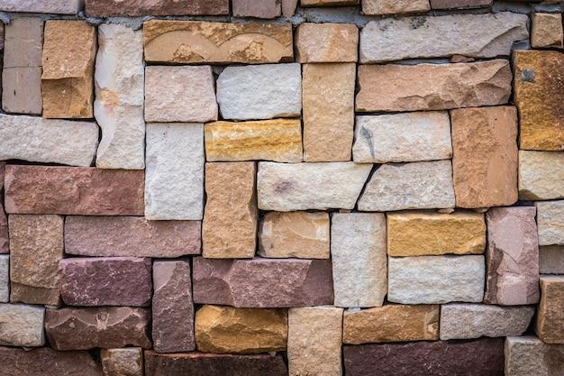 色とりどりの古いレンガ壁の背景のクローズアップ。