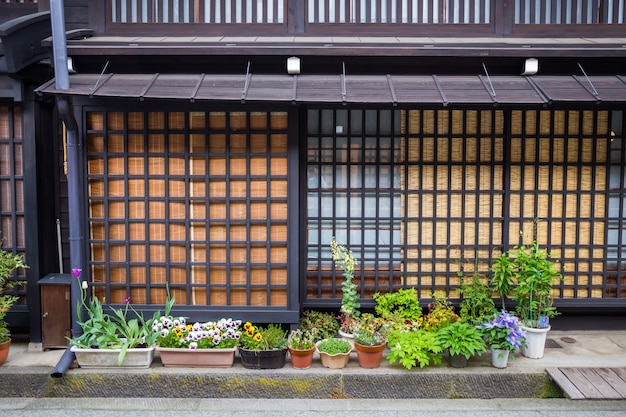 高山の日本の伝統的な家の前の花と装飾的な植物