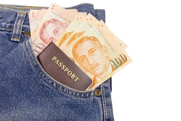 白い背景にあるジーンズポケットのパスポートでシンガポールドルを閉じます