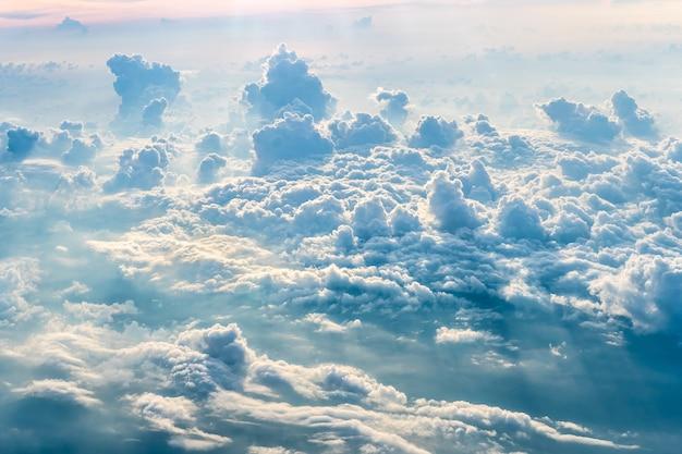 飛行機からの夕方の雲の背景と太陽の青い空