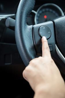 女性の手はステアリングホイールのボリュームコントロールボタンを押します。