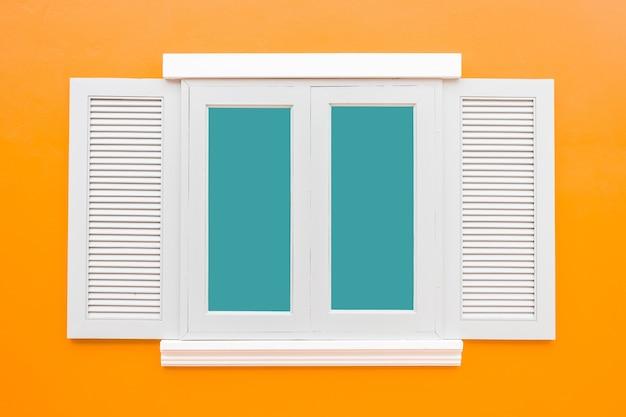 白い窓クラシックヴィンテージ色のオレンジの壁の背景に