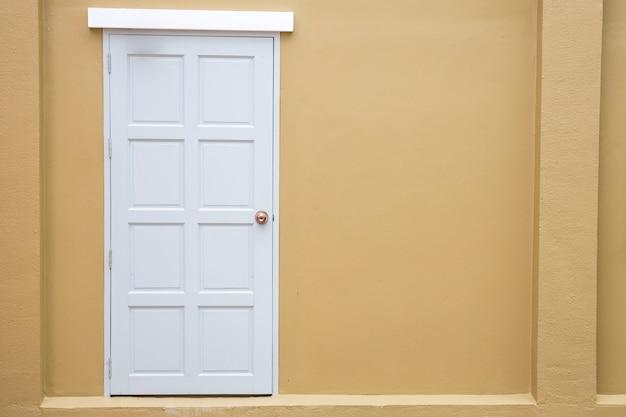 色の黄色の壁の背景に白いドアの古典的なヴィンテージ