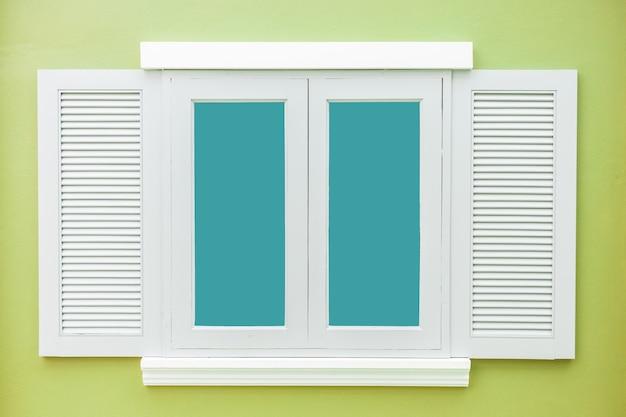 白い窓の色の薄い緑の壁の背景に古典的なヴィンテージ