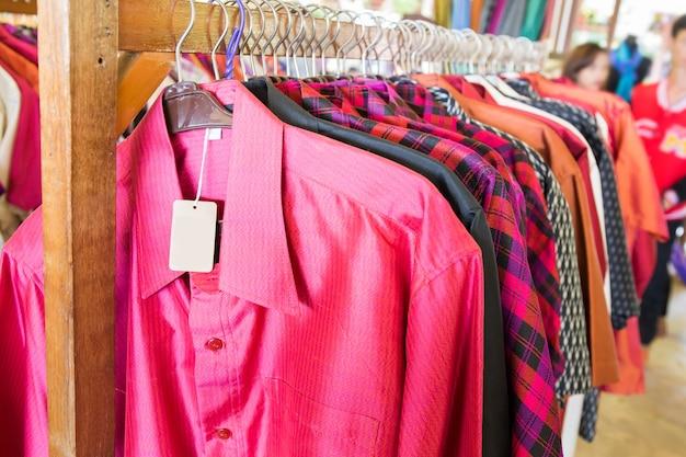 ハンギングレールのシルク製のカラフルなシャツを閉じます。フォーカスを選択