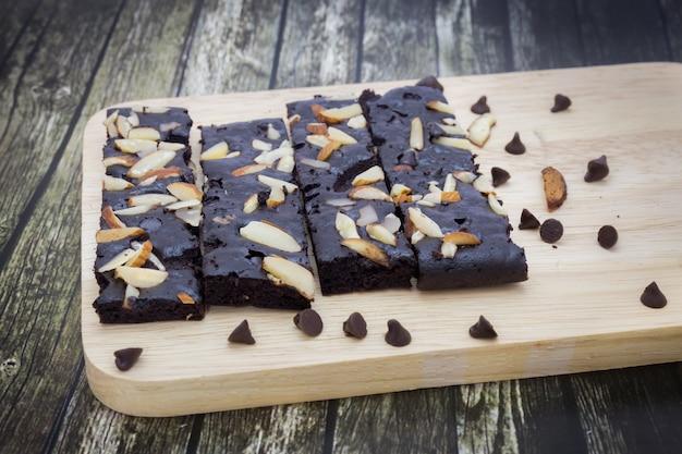 木製のプレートの背景にナッツとケーキのチョコレートブラウニーのクローズアップ