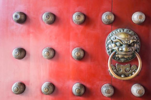 チャイナタウンの伝統的な赤い木製の門のガーディアンブラスハンドル