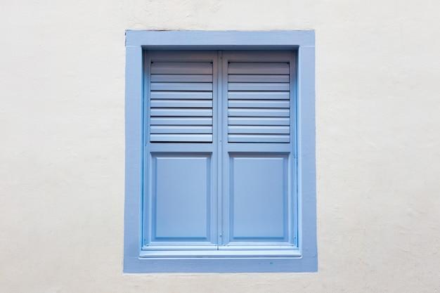 白い木製の窓は、白いセメントの壁の背景に古典的なヴィンテージスタイルです。