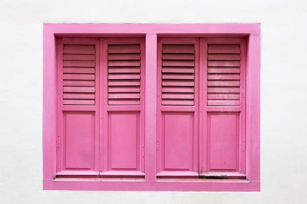 ピンクの木製の窓は、白いセメントの壁の背景に古典的なヴィンテージスタイルです。