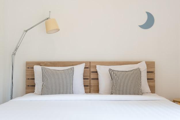 Белый милый интерьер спальни с лампой и деревянный.