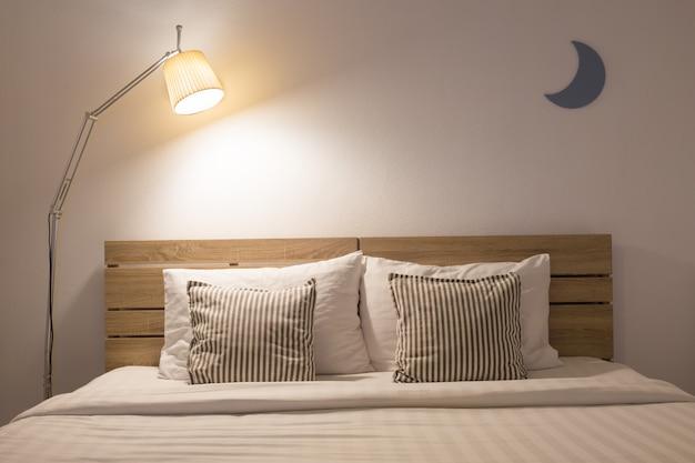 Белый милый интерьер спальни с лампой и деревянное в ночном времени.
