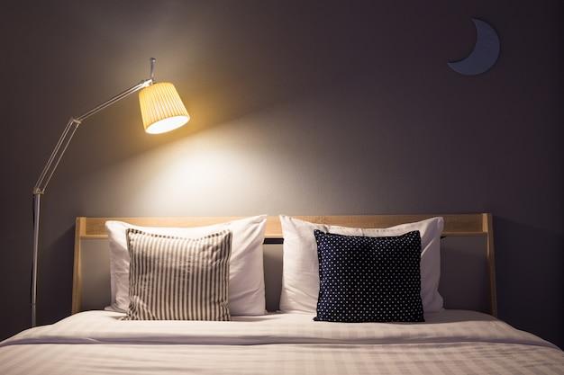 ランプと木の夜の白いかわいい寝室のインテリア。