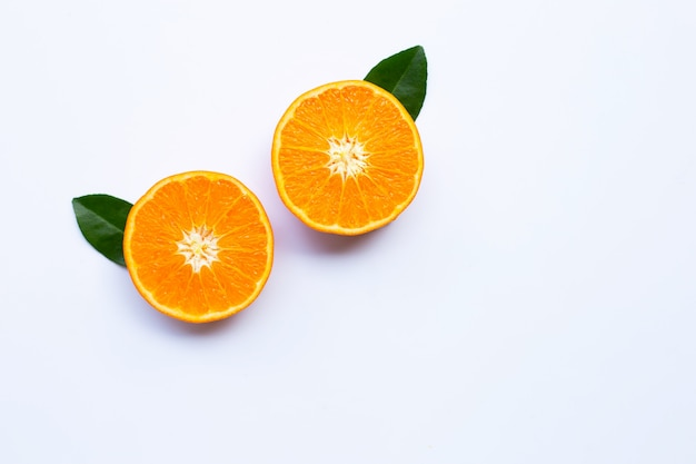 白い背景の上の葉を持つ新鮮なオレンジ色の柑橘系の果物。