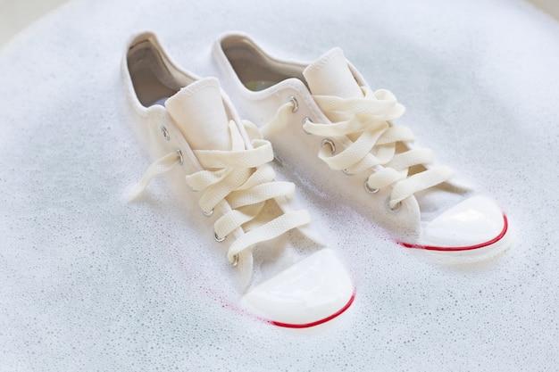 Замочите обувь перед стиркой. грязные кроссовки.