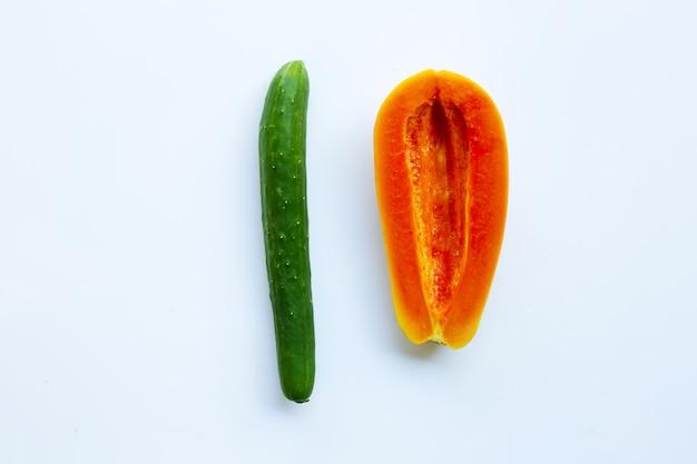 Огурец и папайя на белом фоне. секс концепция