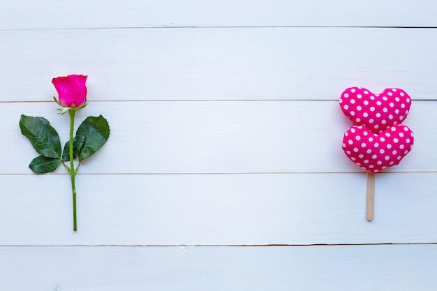 Сердца розы и валентинки на белой деревянной предпосылке.