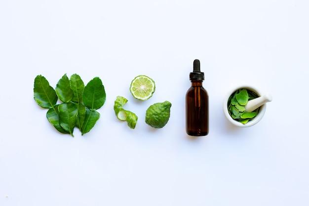 エッセンシャルオイルのボトルと新鮮なカフィアライムまたはベルガモットフルーツの葉